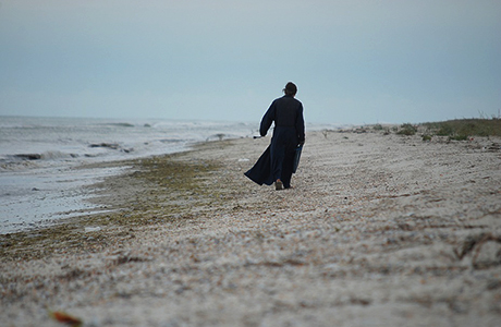 Photo of a monk on the seashore