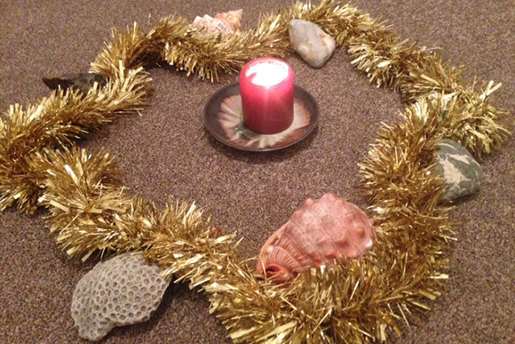 Photo of a seashore wreath: tinsel, pebbles, shells and candle