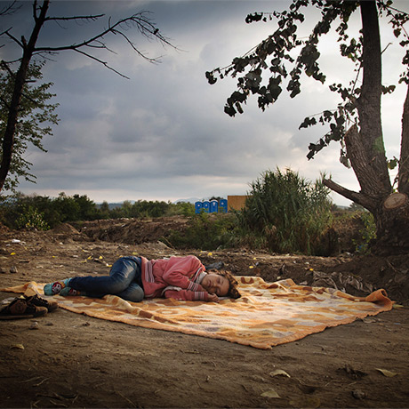 Photo of a woman sleeping outdoors on a rug